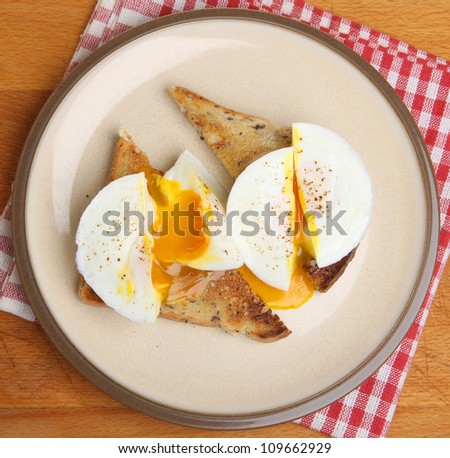 Two poached eggs on whole wheat toast. - stock photo