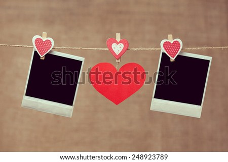 Two polaroid photo frames and red heart for valentines day hanging on vintage background with vintage instagram toning - stock photo