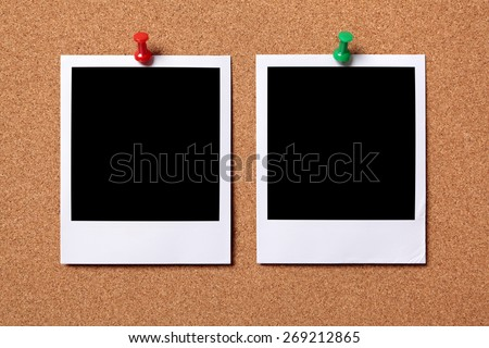 Two polaroid photo prints, pushpin, cork notice board background.   - stock photo
