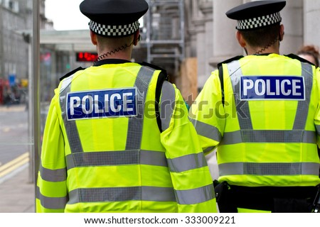 Two police officers in hi-visibility jacket patrolling in the city - stock photo