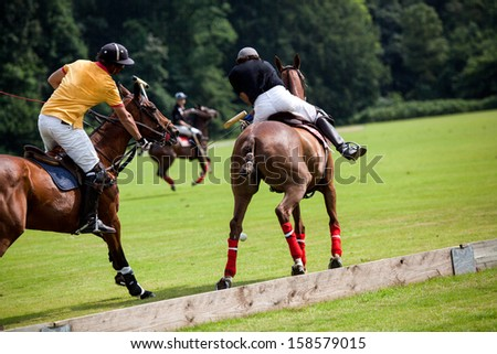 Two Polo Player are braking to get the best position to hit the ball. - stock photo