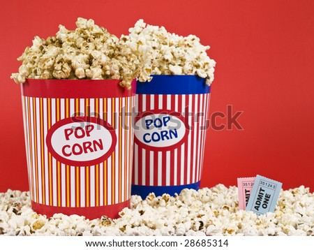Two popcorn buckets over a red background. - stock photo