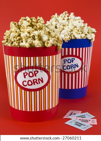 Two popcorn buckets over a red background. Movie stubs sitting aside. - stock photo