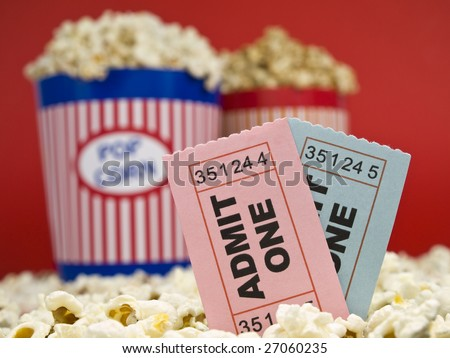 Two popcorn buckets over a red background. Movie stubs sitting over the popcorn.