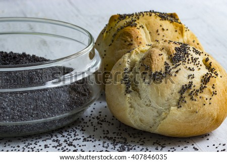 Two poppy bun and a glass bowl with poppy seeds