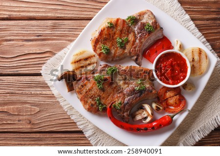 Two pork steak with grilled vegetables on white plate, horizontal view from above - stock photo