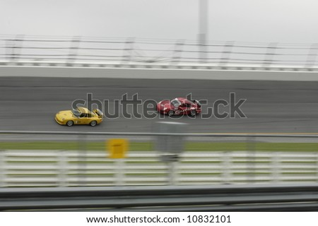 Two Porsche 911's racing on the banks at Daytona International Speedway - Rennsport Reunion III - stock photo