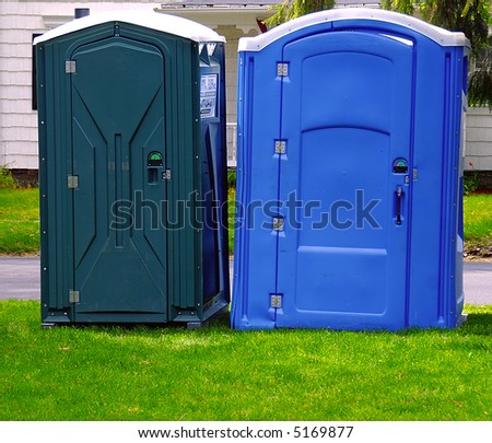 Two portable bathrooms on a cloudy overcast day - stock photo