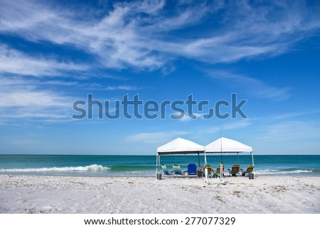 Two Portable Canopy's with Lounge Chairs set up to provide shade on the Beach   - stock photo
