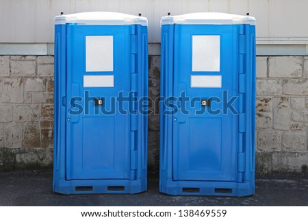 Two portable toilet cabins at construction site - stock photo