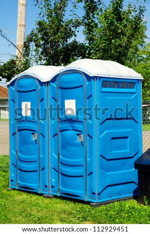 Two portable toilet or loo in blue plastic at a park public event or concert, with white sign on door ready for text. - stock photo