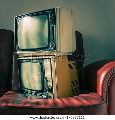 Two portable vintage televisions on red couch - stock photo