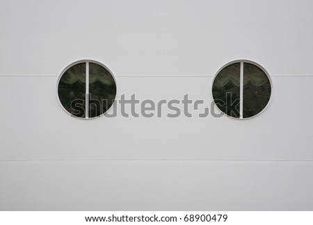 Two portholes in huge white cruiser. Space for text. - stock photo
