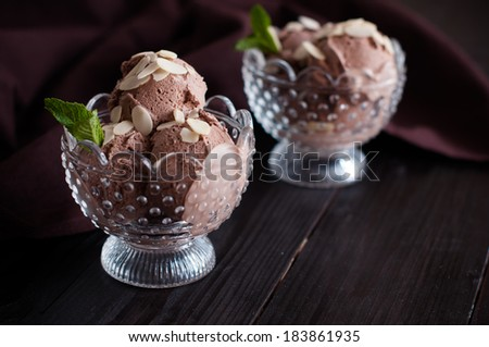 Two portions of delicious chocolate ice cream with almonds and mint leaf in crystal bowls and dark brown cloth on a wooden board, appetizing dessert, food closeup. - stock photo