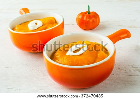 Two portions of pumpkin squash vegetable soup with cream in a orange serving plate with handle, close up. Pumpkin soup. Squash soup. Soup. Creamy soup. Vegetable soup - stock photo