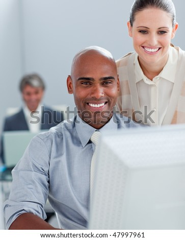 Two positive business colleagues working at a computer in the office