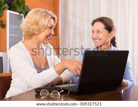 Two positive female pensioners sitting with laptop indoor. Focus on blonde - stock photo