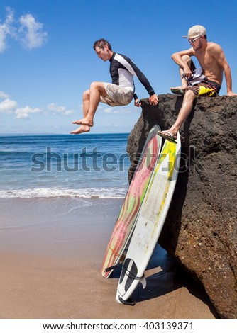 Two positive friends surfer on a rock. Two surfboards standing on the sand, leaning on a rocky big stone - stock photo