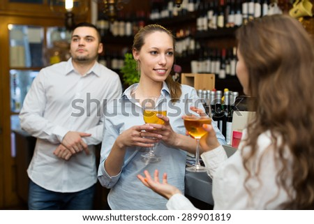 Two positive girls with man chatting at bar of restaurant - stock photo