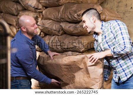 Two positive loaders handling sacks with something heavy indoors - stock photo
