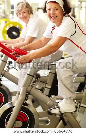 Two positive senior women exercising in gym - stock photo