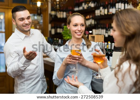 Two positive smiling girls with man chatting at bar of restaurant. Focus on girl - stock photo