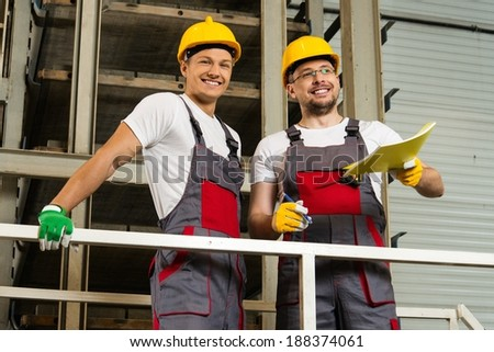Two positive workers  in safety hats on a factory - stock photo