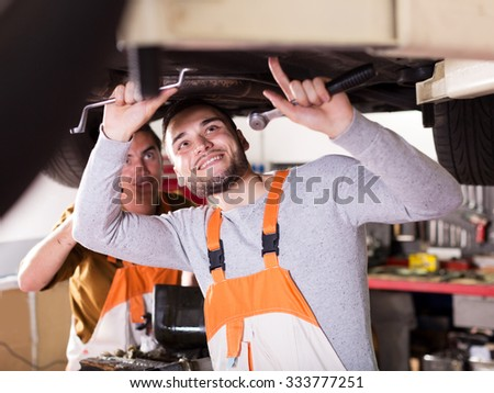 two postive car mechanics at workshop at work - stock photo