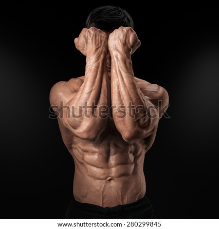 Two Power Hands in Front of Face. Close-up of a man's fists and abs. Strong man's arm with muscles and veins. - stock photo