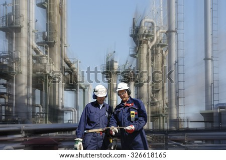 two power industry workers with refinery in the background, slight zoom effect - stock photo