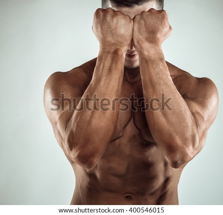 Two Power Mans Hands in Front of Face. Close-up of a man's fists and abs. Strong man's arm with muscles and veins. - stock photo