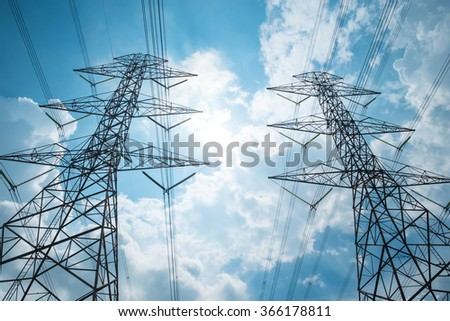 Two power tower against clouds and blue sky - stock photo