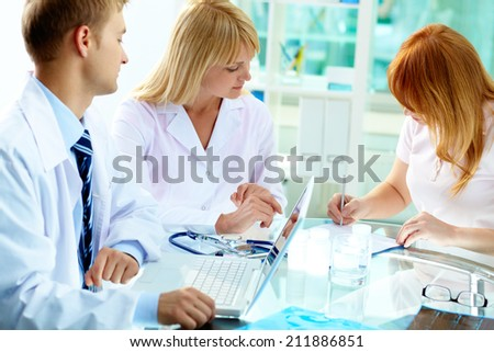 Two practitioners looking at female patient signing paper in hospital - stock photo