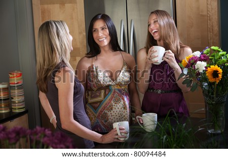 Two pregnant women at different points in their pregnancy with a friend - stock photo
