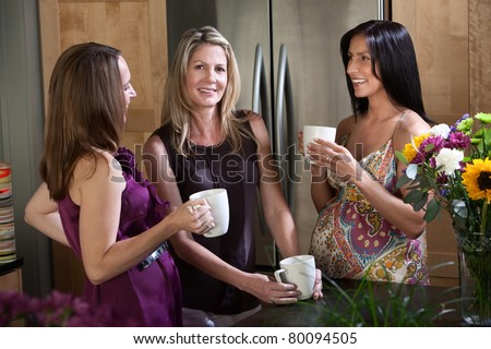 Two pregnant women enjoy cup of coffee or tea with their blonde friend - stock photo