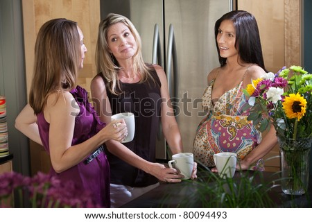 Two pregnant women hold mugs mugs with a friend in the kitchen - stock photo