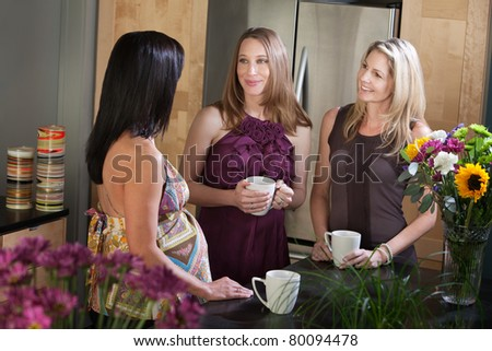 Two pregnant women in a kitchen talk with their friend - stock photo