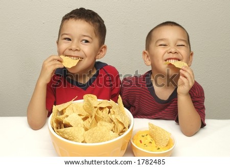 Two preschool brothers enjoy eating tortilla chips and queso - stock photo