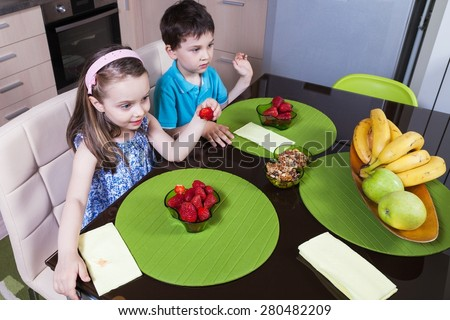 Two preschool children eat strawberry in the kitchen - stock photo