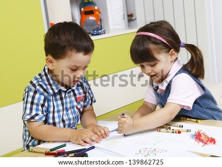 Two preschool children playing with crayons
