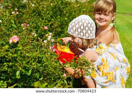 Two preschool girls watering flowers - stock photo