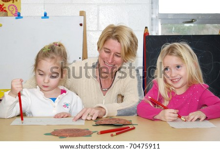 two preschoolers at work with teacher - stock photo