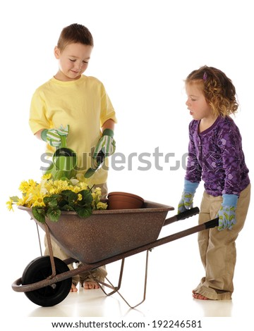 Two preschoolers preparing to work in a spring garden together.  On a white background. - stock photo