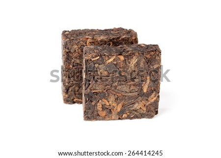 Two pressing briquette of black Chinese Shu Pu Erh tea stand isolated on white background, selective focus with shallow DOF - stock photo