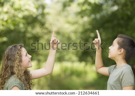 Two preteen girls pointing at copyspace - stock photo