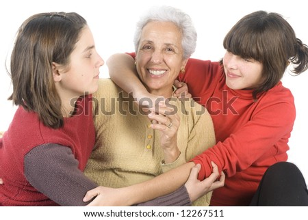 Two pretty adolescent girls embracing their grandmother - stock photo