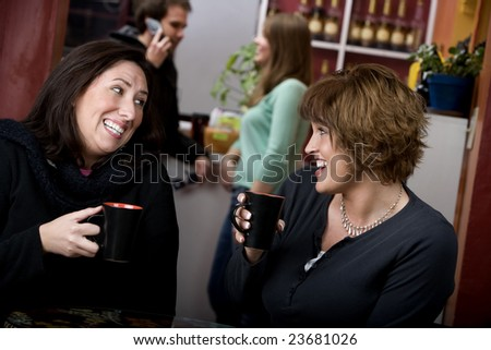 Two pretty adult women in a coffee house - stock photo