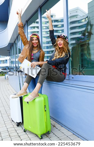 Two pretty best friends girls going crazy about their trip, posing near airport with luggage, urban background. Lifestyle portrait of two sisters enjoying travel. - stock photo