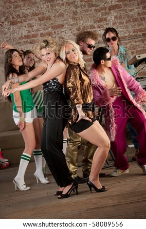 Two pretty blonde girls dancing with others at a 1970s Disco Music Party - stock photo