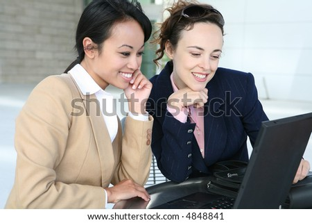 Two pretty business women working on the laptop computer - stock photo